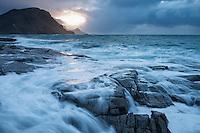 Waves crash over rocky coast of Vestvågøy during winter storm, Lofoten Islands, Norway