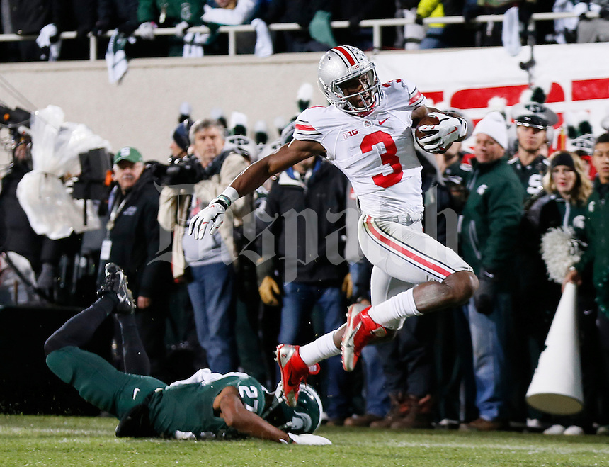 Ohio State Buckeyes wide receiver Michael Thomas (3) escapes tackle by Michigan State Spartans safety Kurtis Drummond (27) on his way to a 79-yard touchdown during the second quarter of the NCAA football game at Spartan Stadium in East Lansing, Michigan on Nov. 8, 2014. (Adam Cairns / The Columbus Dispatch)