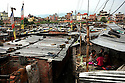 Young kids play in a home in a shantytown in Kathmandu on June 7, 2006. (Photo/Scott Dalton)