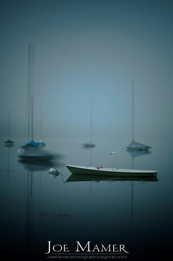 Sailboats on fog shrouded Lake Harriet at dawn.