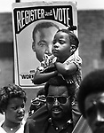 A child sits on her father's shoulders during a civil rights march in Alexandria, VA in the early 1980s.
