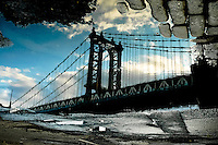Manhattan bridge reflection in a puddle on John Street in DUMBO, Brooklyn, New York, 2008.