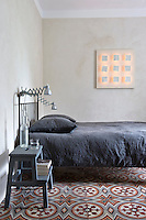 In this bedroom an old set of kitchen steps has been painted and used as a bedside table whilst the colours of the raw plaster walls and dark grey bedding are a pleasing contrast to the old-fashioned cement tiles on the floor