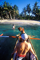 Surfers landing at palm-lined beach in clear water from an outrigger canoe in the Philippines