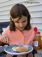 1B15-511z  Child eating breakfast of pancakes with honey, PRA