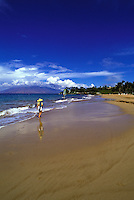 Woman walking on Wailea Beach, Maui, with West Mountains in distance