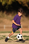 Boy in purple shirt plays soccer in the late afternoon sunlight