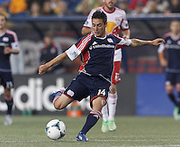 New England Revolution midfielder Diego Fagundez (14) takes a shot. In a Major League Soccer (MLS) match, the New England Revolution (blue) tied New York Red Bulls (white), 1-1, at Gillette Stadium on May 11, 2013.