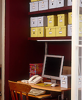 An office has been created in a maroon-painted alcove where simple cardboard boxes on open shelves are an economical and practical storage and filing system