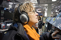 "A customer in a Best Buy store in New York listens on Bose headphones on Saturday, March 31, 2012. Best Buy recently announced that it will be closing 50 of its ""big box"" stores and opening 100 smaller ones.  (© Richard B. Levine)"