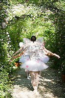Girls dressed as fairies dance under the rose covered archway in dappled sunlight