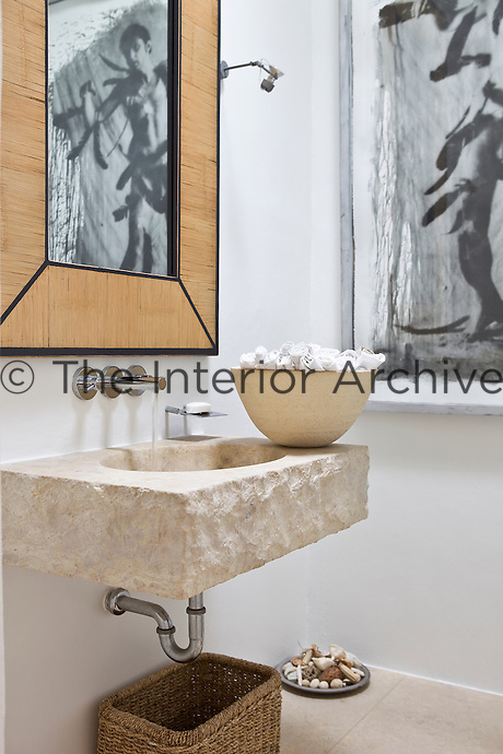 Detail of a basin hewn from a large piece of stone with contemporary chrome taps
