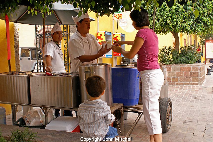 Woman buying ice cream from a street vendor in San Miguel de Allende, Mexico