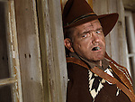 Dramatic portrait of a cowboy leaning against a wall of a wooden house with a cigar in his mouth