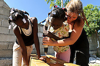Volunteer and young girls building desks at an orphanage supported by EDV, Port-au-Prince, Haiti. EDV is committed to affecting permanent change in disaster-affected communities worldwide. Their role is to facilitate personal connections between volunteers and the survivors of disasters.  The charity is based on a proven model developed by several landmark organisations that have paved the way for citizens to become disaster volunteers. These landmark organisations have shown that supposedly ordinary people working together with the guidance of knowledgeable leaders can make an extraordinary difference in the lives of those affected by disaster..EDV believe that to provide meaningful relief and reconstruction assistance to disaster affected communities they have to do more than reconstruct buildings. They need to understand and address the factors that made a community vulnerable to the disaster in the first place. The charity's work is organised with these factors in mind so that they can affect change that far outlives their presence..EDV believes that survivor motivation is essential to the recovery of any disaster-affected community. Their operations will always be predicated on the idea that survivors may be traumatised, but they are not helpless. With this in mind, EDV encourages host communities to direct their own recovery. EDV believe that this empowerment is essential in helping survivors feel a renewed sense of control over their lives which will, in turn, help overcome the feelings of hopelessness that can follow a disaster and inhibit long term recovery. EDV also believe that social cohesion is of primary importance in any disaster-affected area. No amount of bricks or mortar will bring about sustainable improvement if communities fail to come together or are disrupted by relief efforts. Therefore, their operations will always aim to foster communication and cooperation within and between the communities they serve.