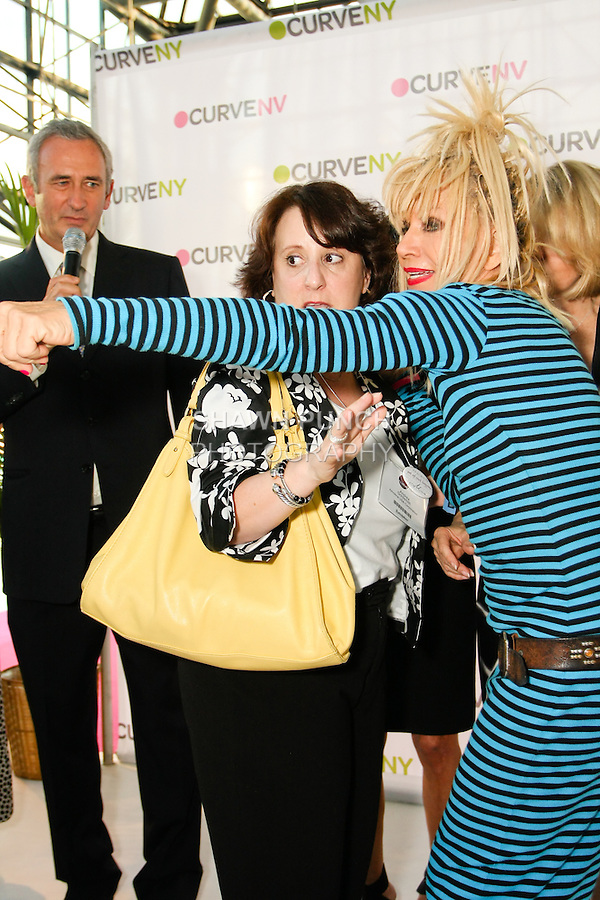Betsey Johnson and Andrea Goldsmith on stage after Ms. Goldsmith won a trip to Paris during the CURVE and CFDA Party For A Cause event during the CURVENY Lingerie & Swim show, at the Jacob Javits Convention Center, August 2, 2010.