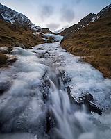 Water flows through a melting mountain stream of ice, Flakstadøy, Lofoten Islands, Norway