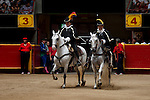 Costumed horse riders enter La Macarena Stadium for the Festival of the Bulls, a month long celebration of bullfighting.