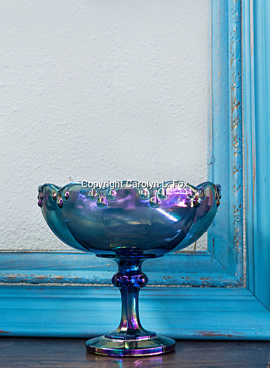 An antique dish sits in front of a picture frame.