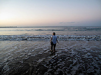 A tourist stands in the shallow water of the Balneario de Luquillo or Luquillo Beach at dusk in Puerto Rico..Photo by Angel Valentin, copyright 2009.