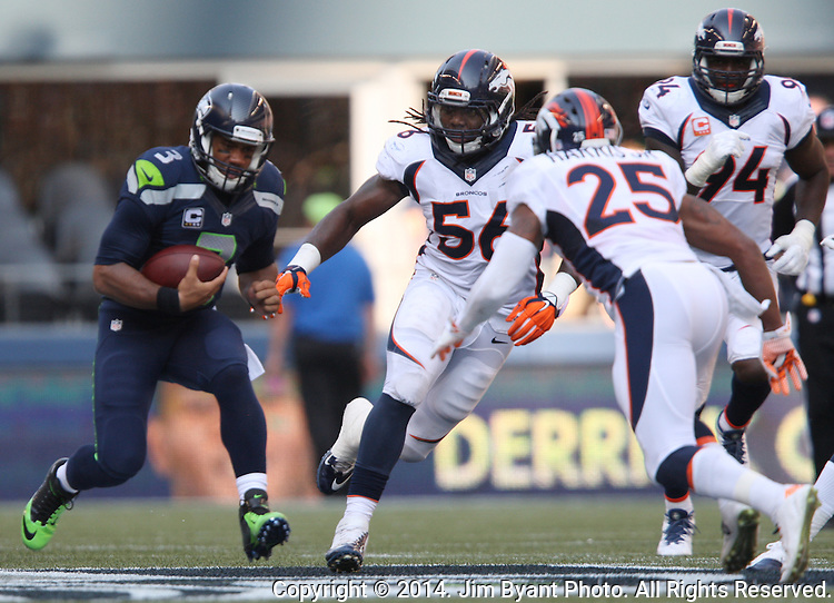 Seattle Seahawks quarterback Russell Wilson (3) scrambles away from the Denver Broncos  linebacker Nate Irving (56) and cornerback Chris Harris Jr. (25) at CenturyLink Field in Seattle, Washington on September 21, 2014.  Wilson completed 24 of 34 passes for 258 yards, two touchdowns and one interception in the 26-20 overtime win against the Broncos.  ©2014. Jim Bryant Photo. All rights Reserved.