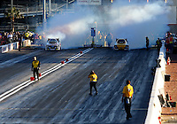 Mar 28, 2014; Las Vegas, NV, USA; NHRA safety safari crews inspect the track as funny car driver Courtney Force (left) does a burnout alongside Del Worsham during qualifying for the Summitracing.com Nationals at The Strip at Las Vegas Motor Speedway. Mandatory Credit: Mark J. Rebilas-USA TODAY Sports
