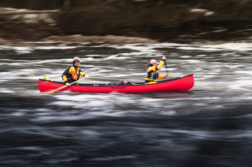 Canoeists with motion blur on a swift section of the Agawa River of Ontario Canada.