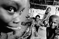 "Guinea. State of ""Guinée Forestière"". Massakoundou. Camp for Sierra Leoneans refugees. Daily life.  Woman and her children near the kitchen space. Family seated on the ground in front of  her clay house. © 2001 Didier Ruef"
