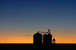 Sunset with silhouetted grain silo for crop storage Eastern Washington State USA