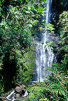 A woman stands on a rock at the base of South Wailua Waterfall. One of Maui's best waterfalls, it is just a few miles past Hana town and is next to the Hana Highway.