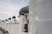 """Indonesia – Sumatra – Aceh – Lampuuk – Sulaiman Amin, the 62-year-old imam prays on the rooftop of the mosque, the only building still standing in the whole village after the tsunami. Amin was caught by the waves in his house, together with his 18-year-old son and his wife. He remembers that the waters had reached the height of the dome. It was the only visible thing in a village that had turned into open sea. Amin ended up five km inland and was rescued in the evening. He had lost his wife, his son and his livelihood, a small rice processing factory for which he never received any compensation. """"Now I have no pension, no income and I have to survive on the alms of the people"""". Three years after the tsunami, Amin was chosen as the new imam from the community, a job he takes very seriously. """"I survived because of God's will"""" he says convincingly."""