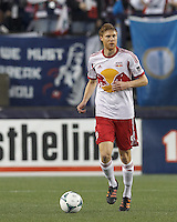 New York Red Bulls defender Markus Holgersson (5) brings the ball forward. In a Major League Soccer (MLS) match, the New England Revolution (blue) tied New York Red Bulls (white), 1-1, at Gillette Stadium on May 11, 2013.