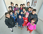 """Children pose for a photo in a church-sponsored """"child-friendly space"""" in the village of Bakhtme, Iraq, which was flooded with displaced families when the Islamic State group took over nearby portions of the Nineveh Plains in 2014. The space is sponsored by the Christian Aid Program Nohadra - Iraq (CAPNI). It includes some children from the host community as well."""