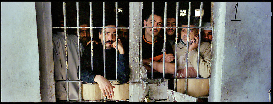 Prisoners - some convicted, others being held for trial - peer through the bars of their cells at the Diyala provincial prison in Baqubah on Mon. Dec. 4, 2006.<br />