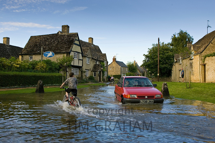 Car and boy on a bike try to move through flood water in Minster Lovell, Oxfordshire, England, United Kingdom