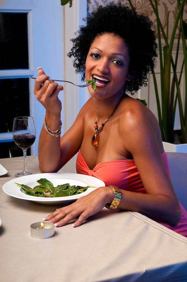 Young woman eats healty salad in a restaurant