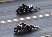 Jul. 20, 2014; Morrison, CO, USA; NHRA pro stock motorcycle rider Eddie Krawiec (near lane) races alongside John Hall during the Mile High Nationals at Bandimere Speedway. Mandatory Credit: Mark J. Rebilas-