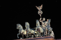 Bronze statue of a quadriga, a chariot pulled by 4 horses, with the goddess Victoria with the Prussian eagle and Iron Cross on her lance, by Johann Gottfried Schadow, on top of the Brandenburg Gate or Brandenburger Tor at night, 18th century, a neoclassical triumphal arch marking one of the old city gates of Berlin, at the end of Unter den Linden, Berlin, Germany. The gate was commissioned by King Frederick William II of Prussia as a sign of peace and built by Carl Gotthard Langhans 1788-91. It stood inaccessible next to the Berlin Wall during Germany's Partition and was restored 2000-02 by the Stiftung Denkmalschutz Berlin. Picture by Manuel Cohen