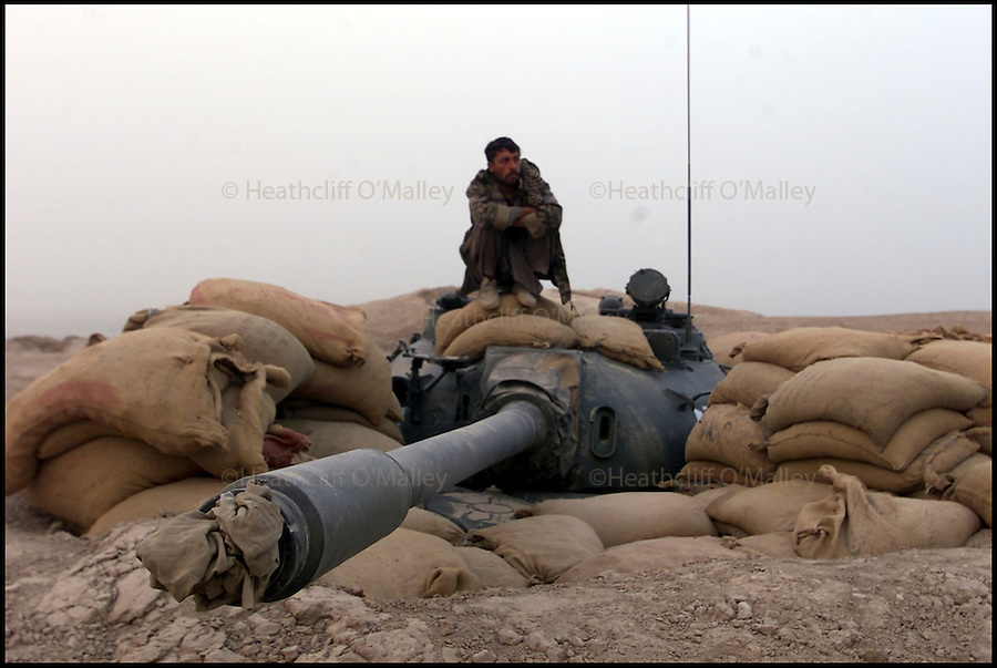 A bored Northern Alliance soldier sits on the turret of a tank on Ay Khanoum, Takhar Province.<br /> <br /> Afghanistan 9 October 2001