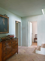 The first floor landing has a terracotta tiled floor arranged in a herringbone pattern and is painted in a light blue limewash