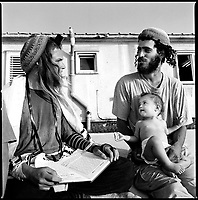 Shirat Ayam Settlement, Gaza strip Israel, Aug. 2005..Waiting for the evacuation. Tomer, right, with his infant son, discusses the Torah with friends in front of the settlement' synagog, hours before being taken away by the army.