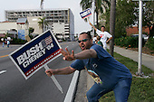 Sarasota, Florida.USA.October 30, 2004..Early voting in Sarasota, Florida. Pro-Bush supporter Mike Boom, an unempoyed funeral home worker,  jesters to passing cars just out side the polling station.