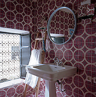 The walls of the bathroom are covered in red and cream tiles with a bold geometric pattern