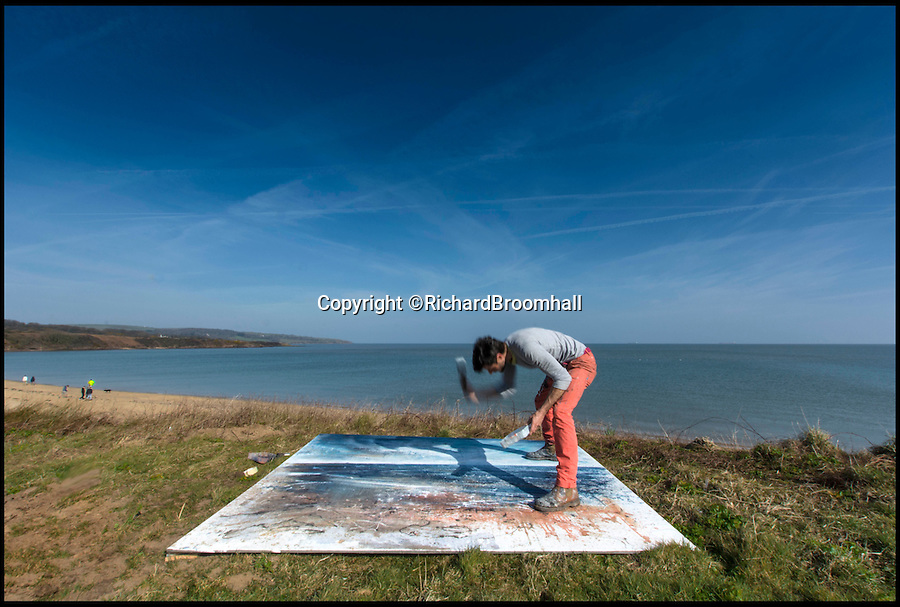 BNPS.co.uk (01202 558833)<br /> Pic: RichardBroomhall/BNPS<br /> <br /> Artist in Residence...Garratt in his element, at work on his Lligwy Bay canvas.<br /> <br /> Artist Anthony Garratt is giving a whole new meaning to landscape painting - his incredible pieces aren't just of the landscape, they're in it too.<br /> <br /> The 35-year-old painter from Bristol has created four canvasses on the island of Anglesey as part of a new outdoor art installation and the paintings will remain in the exact spot they were painted until October.<br /> <br /> Mr Garratt spent several days on each of the giant 8ft-wide scenes, which are exposed to the elements and can be enjoyed by walkers as well as art fans. <br /> <br /> The landscapes had to be created on marine board - a thick marine plywood treated with sealant and epoxy, like a boat - rather than normal canvas, coated with five layers of varnish afterwards and mounted on bespoke steel frames to ensure they survive any harsh outdoor conditions.