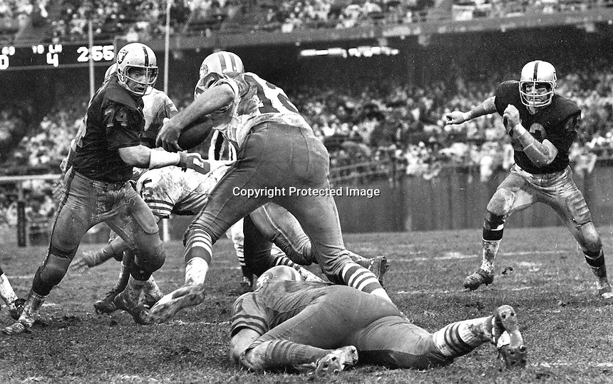 Raiders vs. 49ers ...Tom Keating #74 and #42 Bill Laskey try to get 49er QB John Brodie,,1970 game in Oakland rain. (photo/Ron Riesterer)