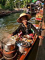 Woman selling food from boat at Damnoen Saduak Floating Market in Ratchaburi, Thailand.