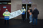 Motherwell 3 Dundee 1, 12/12/2015. Fir Park, Scottish Premiership. Two stewards examine a banner outside the turnstiles at the Davie Cooper Stand at Fir Park, home to Motherwell Football Club, before they played Dundee in a Scottish Premiership fixture. Formed in 1886, the  home side has played at Fir Park since 1895. Motherwell won the match by three goals to one, watched by a crowd of 3512 spectators. Photo by Colin McPherson.