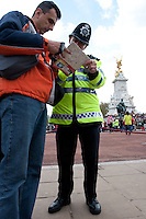 A police officer helps a tourist with his map outside Buckinham Palace in London, UK May 1st 2008