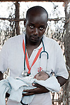 MATHAHALIBAH, KENYA - JULY 4: Umi Adan Olow, 3 months old, is held by Daniel Wanyoike, a community therapeutic nurse for Save the Children on July 4, 2011 in Mathahalibah, Kenya. The child weighed 1,7 kilograms. The team examined about thirty children, among them some severely malnourished. Umis's mother brought her to the outreach site. The child has been sick a lot since birth. Amina Yare Isak, her mother, has two other children in the Save the Children nutrition program. The mother blames the drought for her children's sickness. Her livestock was finished and the lack of milk made her children malnourished. Two successive poor rains, entrenched poverty and lack of investment in affected areas have pushed millions of people into a fight for survival in the Horn of Africa. This is the driest this area have been since sixty years. (Photo by Per-Anders Pettersson)