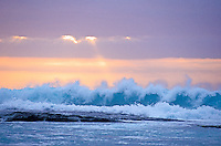 A large frothy wave breaks at the shore with a soft pastel sunset in the background.